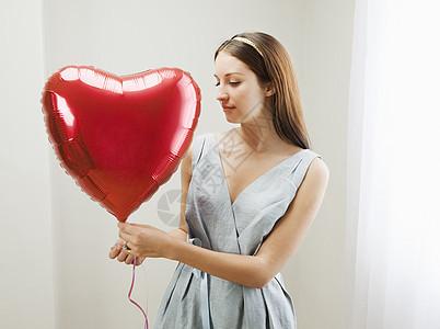 拿着心形气球的女人图片