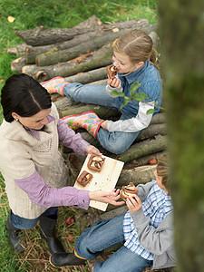 吃苹果蛋糕的妇女和儿童图片