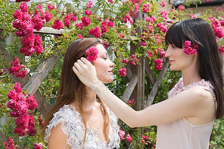 把玫瑰插在朋友头发上的女人图片