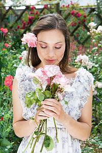 手拿玫瑰闻玫瑰的女人图片