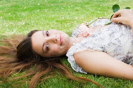 女人拿着玫瑰躺在草地上图片