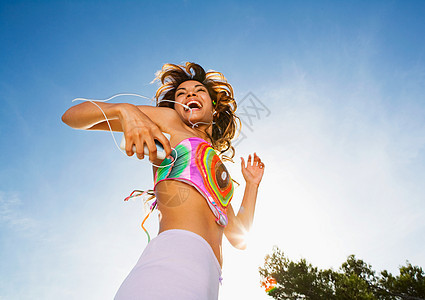 精力充沛的女人对着音乐播放器跳舞图片