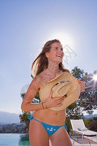 游泳池边的年轻女子图片