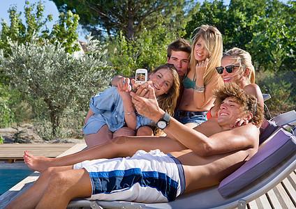 游泳池边的青少年拍照图片