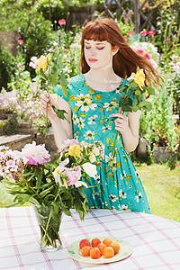 年轻女子在花瓶里插花图片