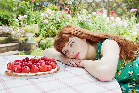 年轻女子看着草莓馅饼图片