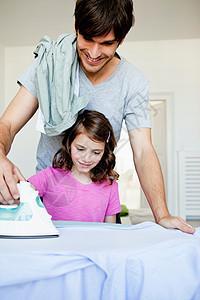 父亲和女孩熨衣服图片