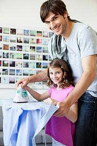 父亲和女儿一起熨衣服图片