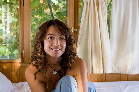 坐在床上微笑的女人图片