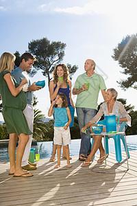 一家人在水池边的木平台上聊天喝饮料图片