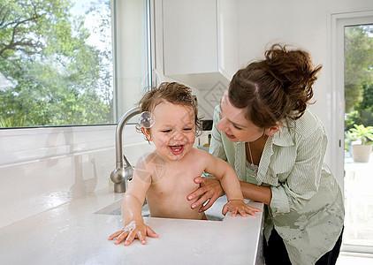 妈妈带着孩子在厨房水槽里洗澡图片