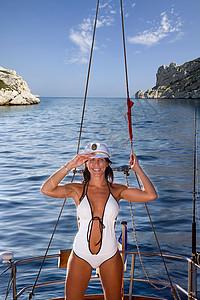 穿泳衣的女性在帆船上敬礼图片