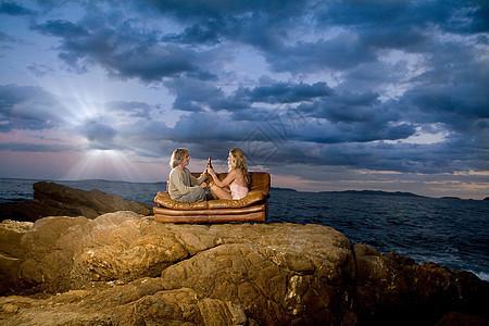 一对夫妇在海边的沙发上烤啤酒图片