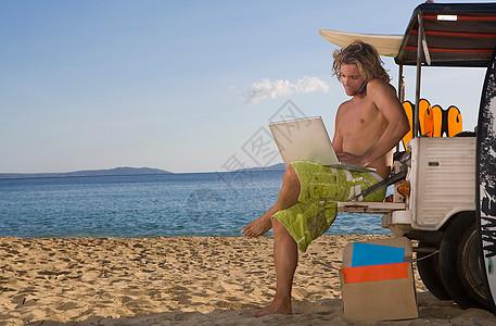 沙滩吉普车上的男人使用笔记本电脑图片