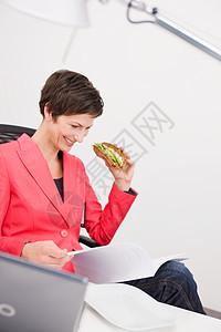 在办公室吃三明治的女人图片