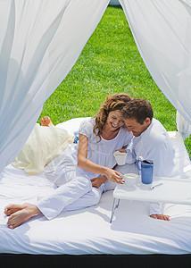 一对夫妇在花园的床上吃早餐图片