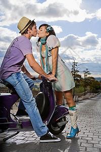 女人亲吻摩托车上的男人图片