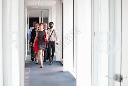 走在走廊上的商业人士图片