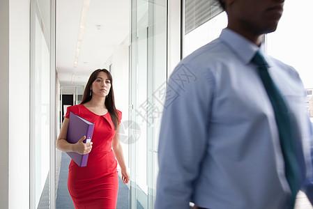两个商务人士走过摄像机图片