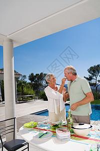 在池边吃东西的男人和女人图片