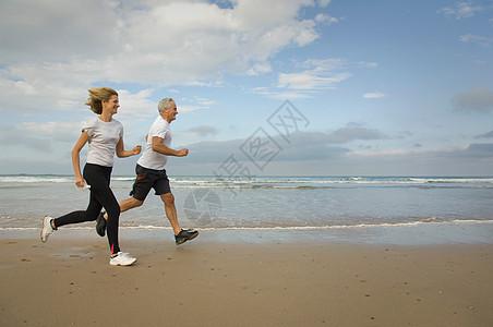 一对夫妇在海滩上奔跑图片