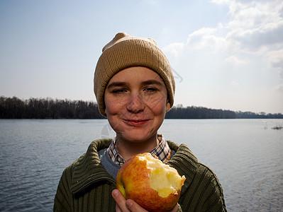 在河边拿着苹果的男孩图片