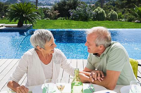 游泳池边的男人和女人交谈图片