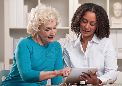 两名使用数字平板电脑的女性图片