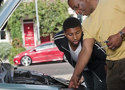 父亲和儿子在维修汽车发动机图片