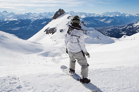 男子在山顶玩滑雪板图片