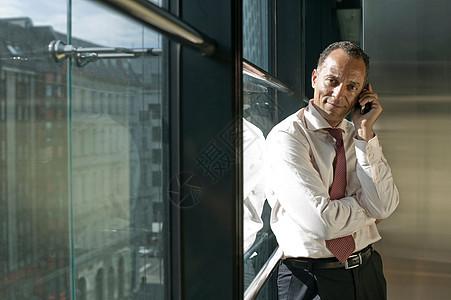 男人靠在窗边打电话图片