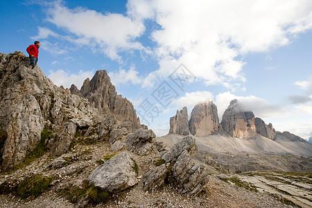 站在岩石上看山峰的人图片