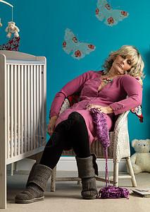熟女睡在婴儿床旁边的椅子上图片