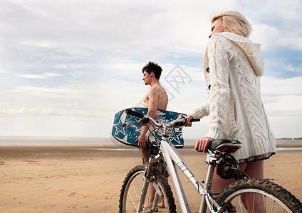 在海滩骑着自行车的情侣图片