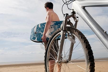 在海滩上骑自行车和冲浪板的男人图片