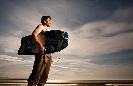 海滩上有布吉冲浪板的男人图片