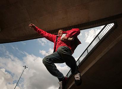 十几岁的男孩拿着书蹦蹦跳跳图片