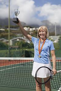 网球场上拿奖杯的老妇人图片