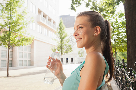 坐在长椅上喝水的女人图片