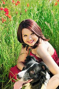 女人和狗坐在田里图片