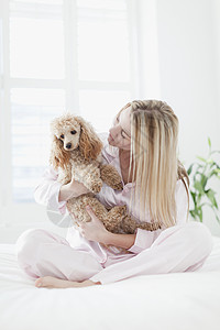 在床上抱着狗的女人图片