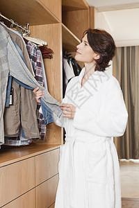 从衣橱里挑衣服的女人图片