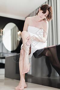 女人在擦她腿上的乳液图片