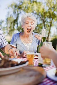在野餐桌上吃饭的老女人图片