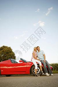 坐在电动跑车上的夫妇图片