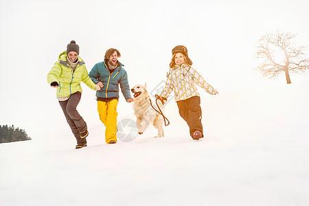 一家人和狗在雪上奔跑图片