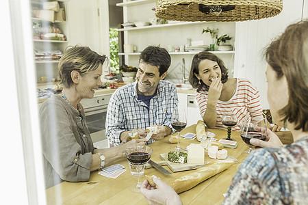 在餐桌上喝红酒和打牌的成年朋友图片