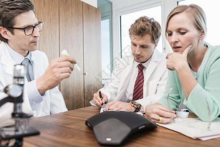 科学家们坐在桌子旁看试管图片