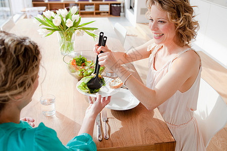 两个女人坐在桌上吃沙拉图片