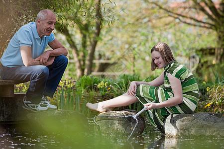 池塘边的老人和年轻女孩图片